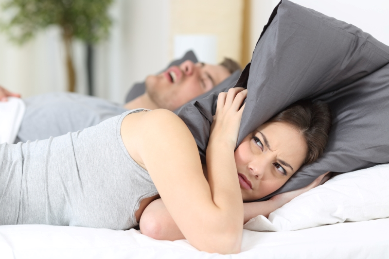 woman holding pillow over her head
